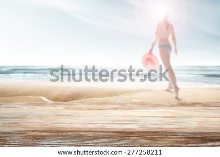 woman with pink hat on beach  and wooden desk