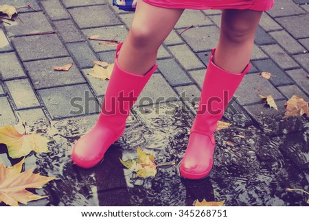 Woman with pink rain boots jumps into a puddle. Toned image