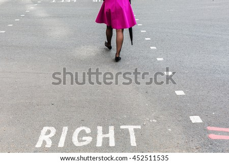 woman with pink skirt crossing a street in the city