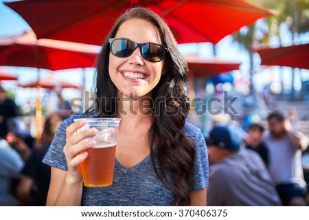 woman with plastic cup of beer at outdoor bar or pub - stock photo