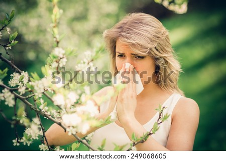 Woman with pollen allergy in springtime near tree in bloom.  - stock photo