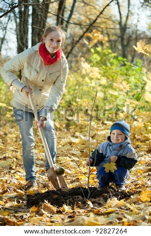 woman with  preschooler son setting tree in autumn garden - stock photo