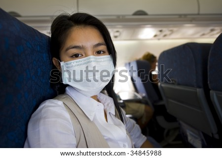 woman with protective mask in an airplane - stock photo