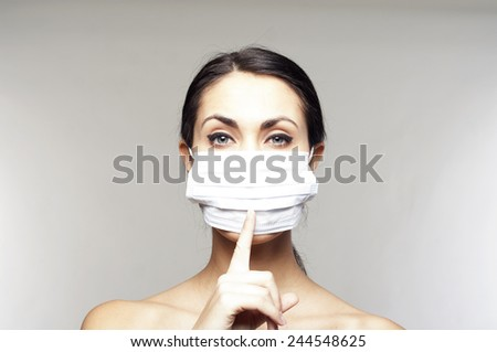 Woman with protective mask saying shh over grey background - stock photo