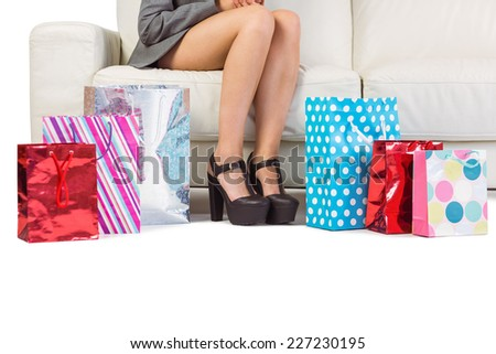 Woman with purchases and shopping bag on the floor at home - stock photo
