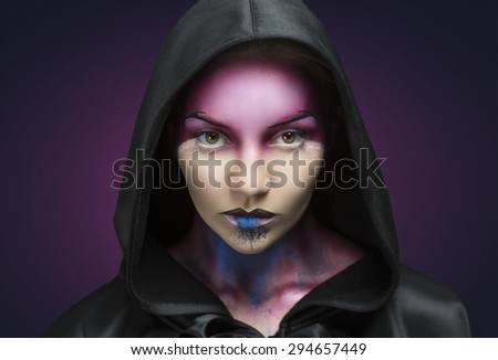 Woman with purple blue face art and big black hood. Mystery girl creative idea to Halloween party. Beauty close up portrait, perfect facial skin, crazy creature. Cosmetics textures on lips and throat  - stock photo