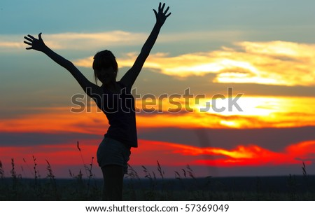 Woman with raised hands on meadow with herbs under sunset light - stock photo