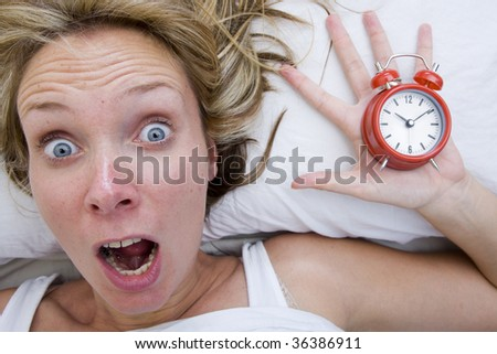Woman with red alarm clock representing lateness or a deadline