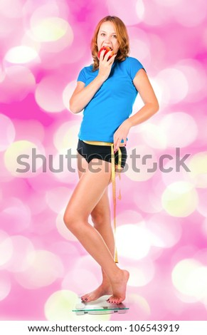 Woman with red apple crouching on scale - stock photo
