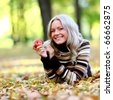 woman with red apple in autumn park - stock photo