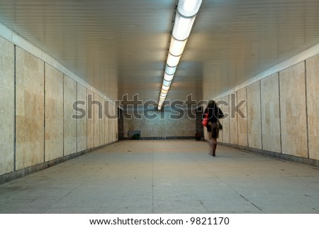 Woman with red bag going through underground passage - stock photo