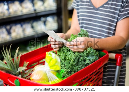 Woman with red basket holding list in supermarket - stock photo