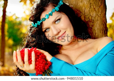 Woman with red berries of Viburnum on outdoors background - stock photo