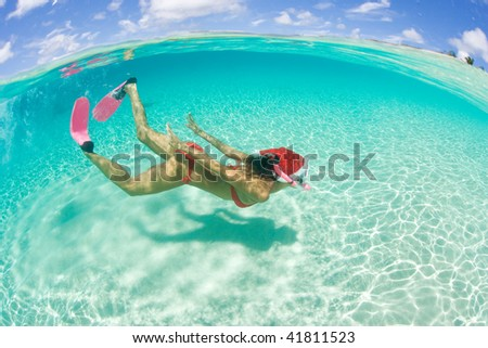 woman with red bikini snorkeling with holiday christmas hat underwater in tropical island paradise