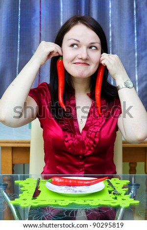Woman with red chili peppers on the kitchen - stock photo