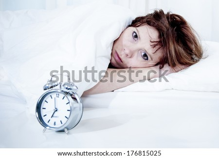 woman with red hair in her bed with insomnia and nightmare can't sleep waiting for her alarm clock to go off on a white background - stock photo