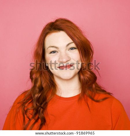 Woman with red hair on pink background - stock photo