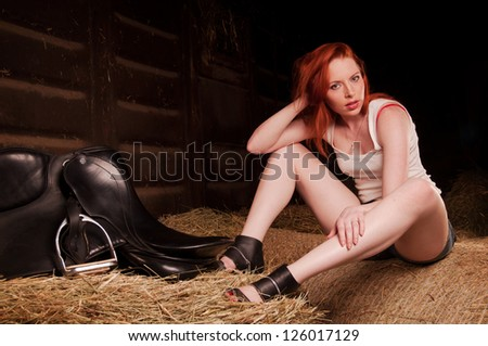 woman with red hair sitting on a haystack
