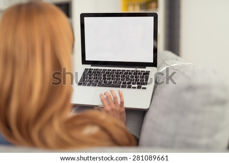 Woman with Red Hair Sitting on Sofa with Laptop Computer, Perspective from Behind Over Shoulder Looking at Blank Computer Screen - stock photo