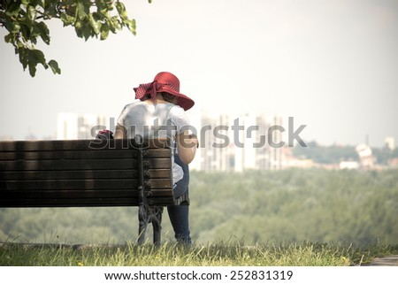 woman with red hat sitting on a bench of Kalemegdan Fortress of Belgrade  - stock photo