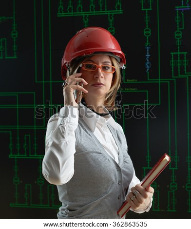 Woman with red helmet make call in power distribution control center - stock photo