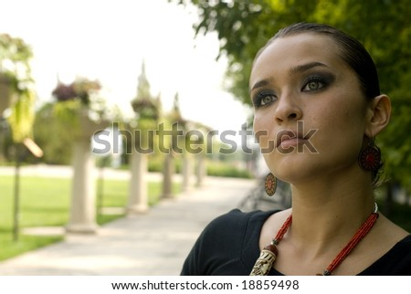 Woman with red jewelry sitting in a park on a sunny day - stock photo