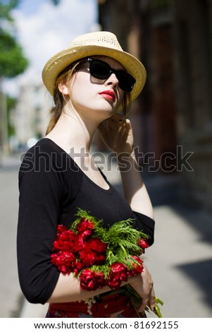 Woman with red lipstick in sunglasses and straw hat enjoying summer day - stock photo