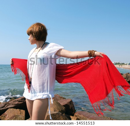 Woman with red pareo in a rocky beach - stock photo