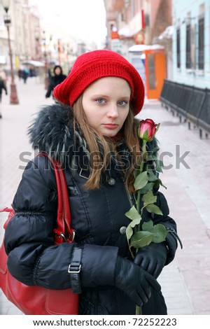 Woman with red rose in winter city