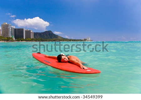 woman with red surfboard in waikiki oahu