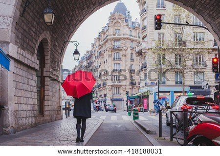 woman with red umbrella walking on the street of Paris, France - stock photo