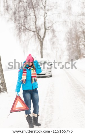 Woman with reflector triangle car snow breakdown problem winter traffic - stock photo