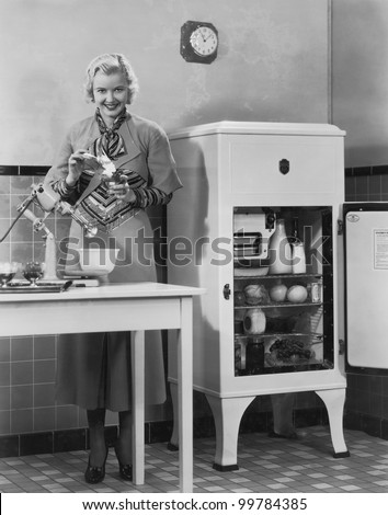 Woman with refrigerator and mixer in kitchen - stock photo