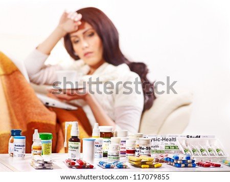 Woman with remedy having  flue in bed. Indoors. - stock photo