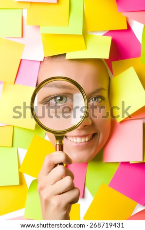 Woman with reminder notes and magnifying glass - stock photo