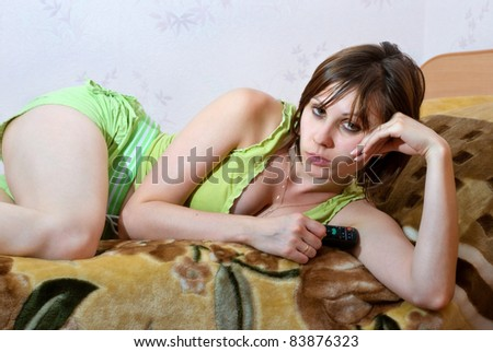 Woman with remote control in hand watching TV while lying on the bed. - stock photo