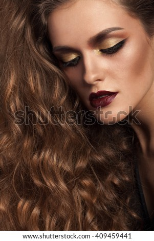 Woman with rich hair and gorgeous hairstyle and gold make up in studio