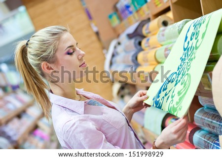Woman with rolls of wallpaper - stock photo