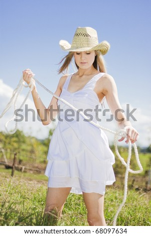 Woman With Rope Working On A Green Grass Farm Paddock Living Life On The Land - stock photo