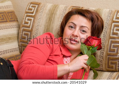 Woman with rose rests upon sofa