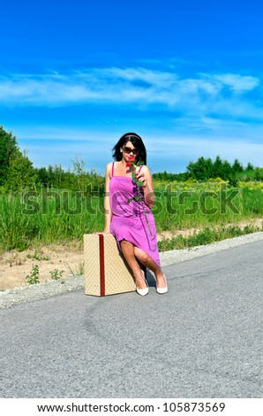 Woman with rose sitting on suitcase on the road. - stock photo