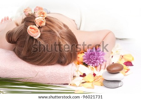 Woman with roses in her hair resting while getting SPA massage - stock photo