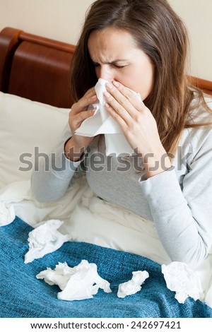 Woman with runny nose and a lot of tissues