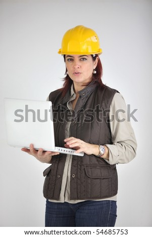 Woman with safety helmet holding a laptop computer on gray background - stock photo