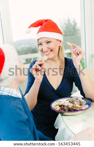 Woman with Santa Cap Eat Christmas Cookies - stock photo