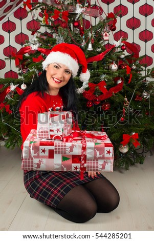 Woman with Santa hat giving Christmas gifts