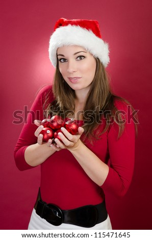 Woman with Santa Hat holding christmas balls on a red background - stock photo