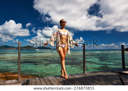 Woman with sarong on a tropical beach jetty at at Seychelles, La Digue. - stock photo