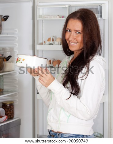 woman with saucepan  near refrigerator  at home - stock photo