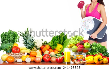 Woman with scales and dumbbell fruits and vegetables background - stock photo